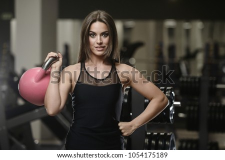 Beautiful strong sexy athletic muscular young caucasian fitness girl workout training in the gym on diet pumping up abs muscles and posing bodybuilding health care and fitness concept #1054175189
