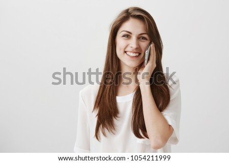 Let me finish this call. Studio shot of charming friendly girl with brown hair talking on smartphone and smiling broadly, gazing at camera, having conversation with best friend over gray background #1054211999