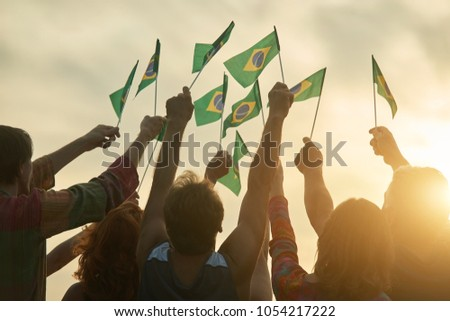 Rising up brazil flags. Crowd of people holding brazilian flags, back view. #1054217222