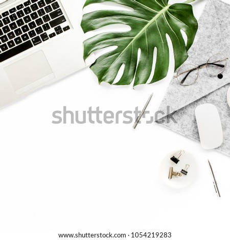 Home office workspace mockup with laptop, tropical leaves Monstera, notebook and accessories on white background. Flat lay, top view #1054219283