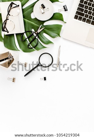 Home office workspace mockup with laptop, tropical leaves Monstera, notebook and accessories on white background. Flat lay, top view #1054219304