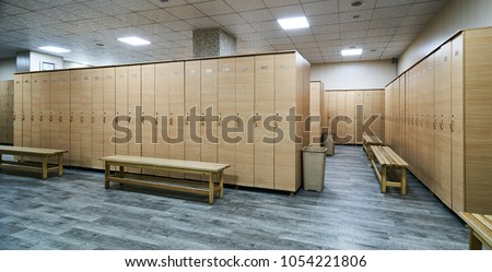 Wooden lockers with a wood bench in a locker room with doors closed. Locker room interior in modern fitness gym  #1054221806