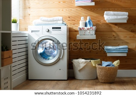 Interior of a real laundry room with a washing machine at the window at home Royalty-Free Stock Photo #1054231892