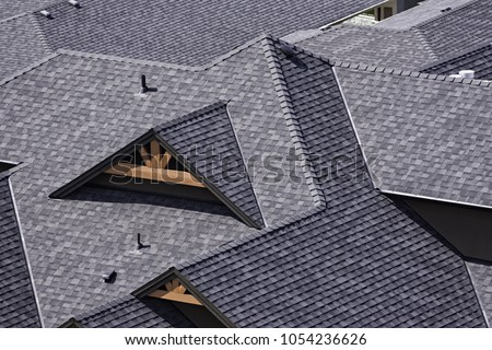 Rooftop in a newly constructed subdivision in Kelowna British Columbia Canada showing asphalt shingles and multiple roof lines Royalty-Free Stock Photo #1054236626