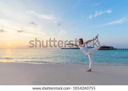 Healthy Beautiful Attractive Asian woman wearing white shirt practicing yoga Standing bow pulling pose on the beach in Maldives with sunset,Feeling so comfortable and relax in holiday #1054260755
