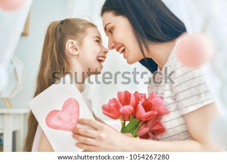 Happy women's day! Child daughter is congratulating mom and giving her flowers tulips. Mum and girl smiling and hugging. Family holiday and togetherness. #1054267280
