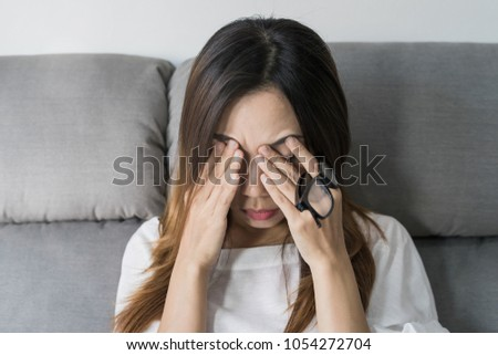 Young woman rubbing her eyes feel painful and take off her glasses siiting on sofa and rest one's eyes at home, Vision problem #1054272704