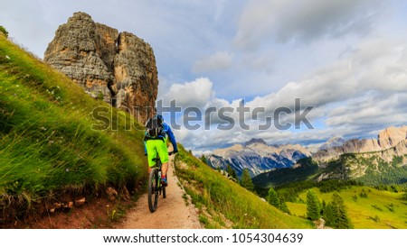 Tourist cycling in Cortina d'Ampezzo, stunning Cinque Torri and Tofana in background. Man riding MTB enduro flow trail. South Tyrol province of Italy, Dolomites. #1054304639