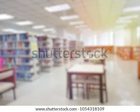 Blurred of the interior of the public library with wooden tables, chairs and books in bookshelves. Education and book's day background concept.   #1054318109