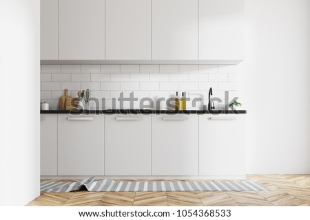 Modern kitchen interior with white brick walls, white countertops and a wooden floor with a rag on it. 3d rendering mock up #1054368533