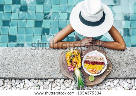 Girl relaxing and eating fruit plate by the hotel pool. Exotic summer diet. Tropical beach lifestyle. Royalty-Free Stock Photo #1054375334