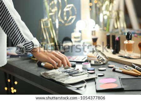 Professional makeup artist near dressing table with decorative cosmetics in beauty salon #1054377806