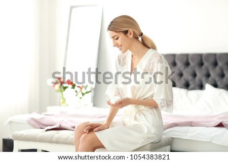 Young woman with jar of body cream at home #1054383821