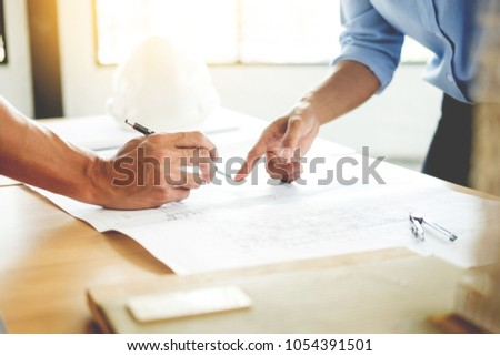 Close-up Of Person's engineer Hand Drawing Plan On Blue Print with architect equipment, Architects discussing at the table, team work and work flow construction concept. #1054391501