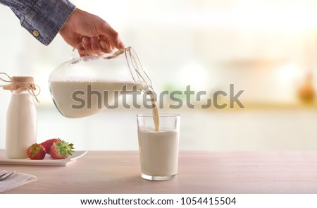 Serving breakfast milk with a jug in a glass on a white wooden kitchen table. Horizontal composition. Front view #1054415504