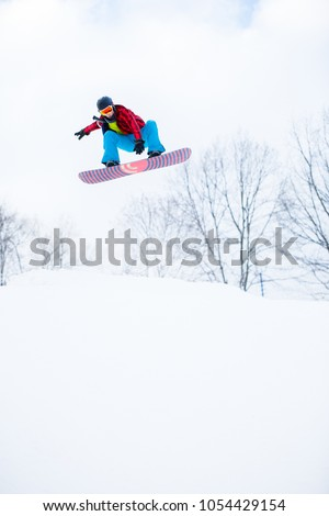 Image of sporty man in helmet with snowboard jumping in snowy resort #1054429154