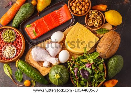 Keto diet concept. Ketogenic diet food. Balanced low-carb food background. Vegetables, fish, meat, cheese, nuts on a dark background. #1054480568