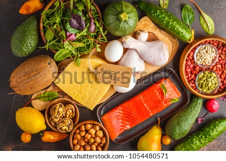 Keto diet concept. Ketogenic diet food. Balanced low-carb food background. Vegetables, fish, meat, cheese, nuts on a dark background. #1054480571