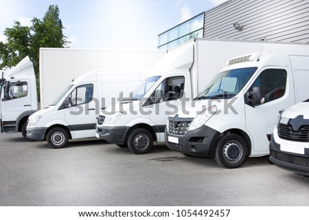 white delivery vans truck on parking in front on the entrance a warehouse at distribution van center #1054492457