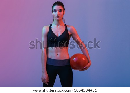 Photo of serious young sports woman standing with ball isolated over purple wall background. Looking camera. #1054534451