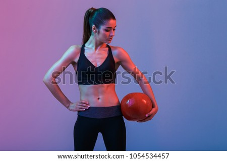 Image of strong young sports woman standing with ball isolated over purple wall background. Looking aside. #1054534457