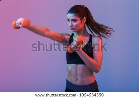 Photo of serious young sports woman make exercises with dumbbells isolated over purple wall background. Looking aside. #1054534550