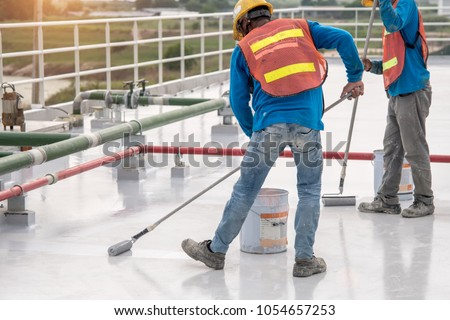 Construction worker coating epoxy paint at roof slab for water proof protection #1054657253