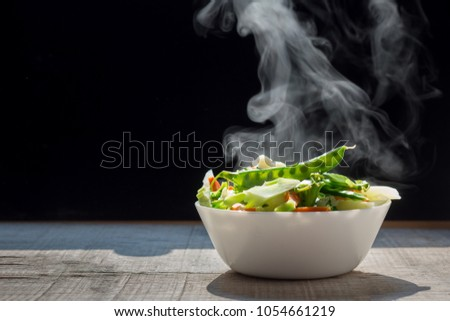 The steaming hot  from Mixed vegetables on white bowl dark background selective focus. #1054661219