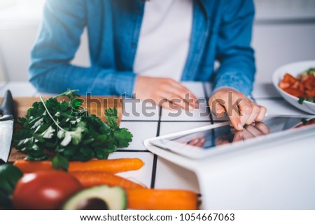 Closeup of young female typing text message in internet searching for healthy recipes, food blogger posting text about vegetarian food, eating raw food lifestyle #1054667063
