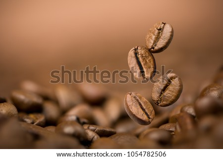 Brown roasted coffee beans falling on pile. Represent breakfast, energy, freshness or great aroma,Flying on dark background with copy space, close-up  #1054782506