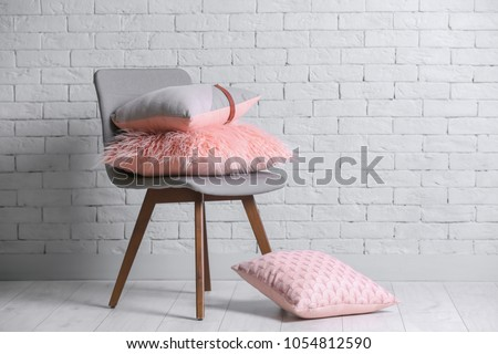 Different pillows on chair in room #1054812590