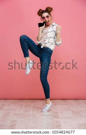 Full length portrait of an excited young girl having fun while listening to music with earphones and mobile phone isolated over pink background