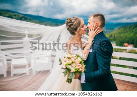 bride and groom in carpathians, mountains, beautiful nature, landscape, scenery. Newlyweds at mountain terrace. Windy veil. Tender picture.