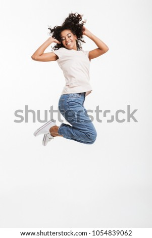Full length portrait of adorable american woman with afro hairstyle wearing jeans and t-shirt jumping and rejoicing with perfect smile isolated over white background #1054839062