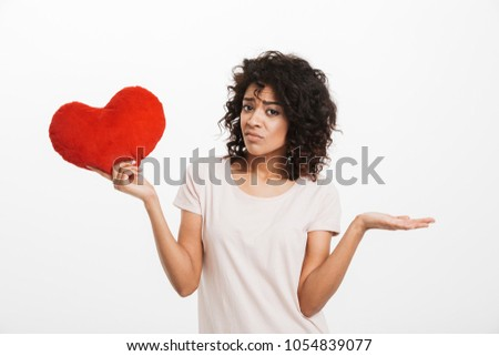 Picture of displeased american woman 20s with brown hair holding red heart shape pillow and expressing sadness isolated over white background