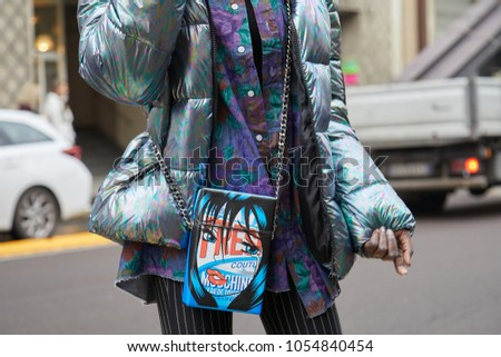 MILAN - FEBRUARY 22: Woman with iridescent gray padded jacket and Moschino blue bag before Max Mara fashion show, Milan Fashion Week street style on February 22, 2018 in Milan. #1054840454