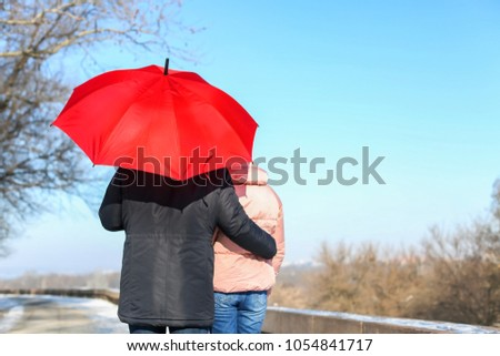 Young romantic couple with bright umbrella walking on sunny winter day #1054841717