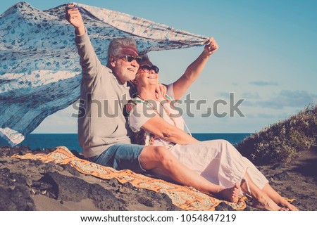 freedom and rebel hippies man and woman senior aged 70 years old. rest at the beach and enjoy freedom and the good weather. #1054847219