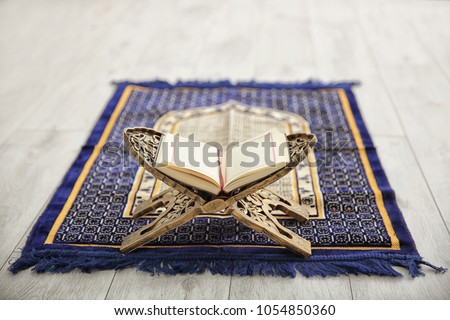 Opened Quran on Muslim prayer mat indoors Royalty-Free Stock Photo #1054850360