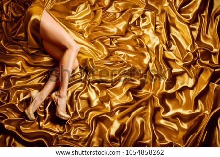 Woman Leg on Gold Silk Fabric Background, Sexy Fashion Model Legs in Golden Shoes lying over Waving Satin Cloth #1054858262