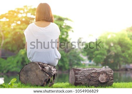 girl sitting alone in the park on sunset #1054906829