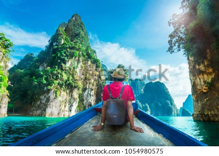 Man traveler relaxing on boat and joy view of limestone mountain, Cheow Lan lake, Ratchaprapha dam, Surat Thani, Travel nature Thailand, Beautiful destination place Asia, Outdoor vacation travel trip #1054980575