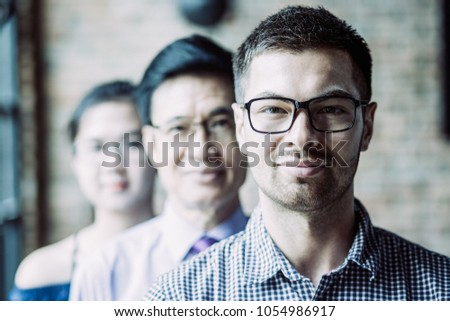 Closeup of three content adult business people standing in row and looking at camera. People in background are blurred. Front view. #1054986917