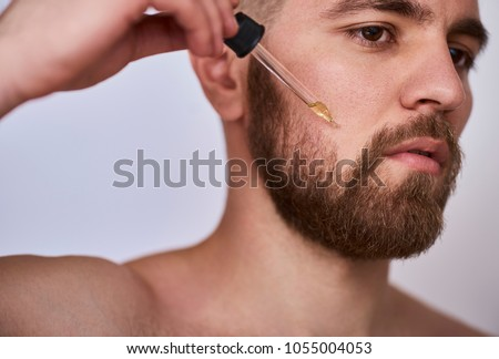 close up image of handsome man with pipette with beard oil #1055004053