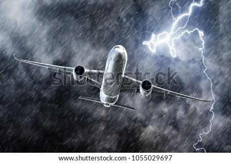Powerful thunderstorm lightning strike and heavy rain in the sky passenger airplane Royalty-Free Stock Photo #1055029697