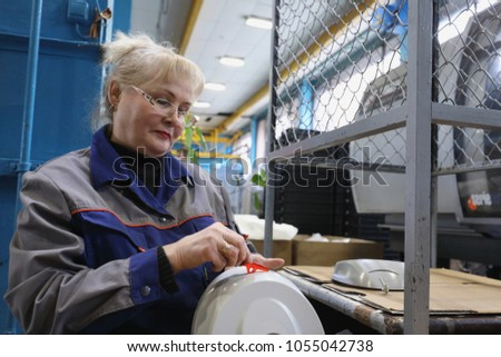 ST. PETERSBURG, RUSSIA - MARCH 15, 2018: Female worker at work in the plastics recycling plant named after newspaper Komsomolskaya Pravda. The plant produces plastic products since 1931 #1055042738