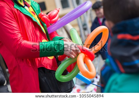 A freelance clown creating balloon animals and different shapes at outdoor festival in city centre. School bag, angel wings, butterflies and dogs made of balloons. Concept of entertainment, birthdays Royalty-Free Stock Photo #1055045894
