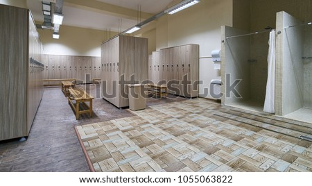 Public shower interior with everal showers, toilet sink and lockers in locker room in luxury fitness spa centre Royalty-Free Stock Photo #1055063822