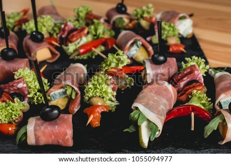 spanish snack, banderillas on skewers with jamon, ramses, pear, dorblue, chorizo, dried tomato, champignon, pickling olives, garlic, pickles, gouda, green, onion and red pepper #1055094977
