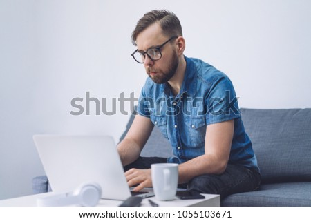 Young businessman working on the laptop concentrated on his project. Blank white wall on the background. Copy space for your text. #1055103671